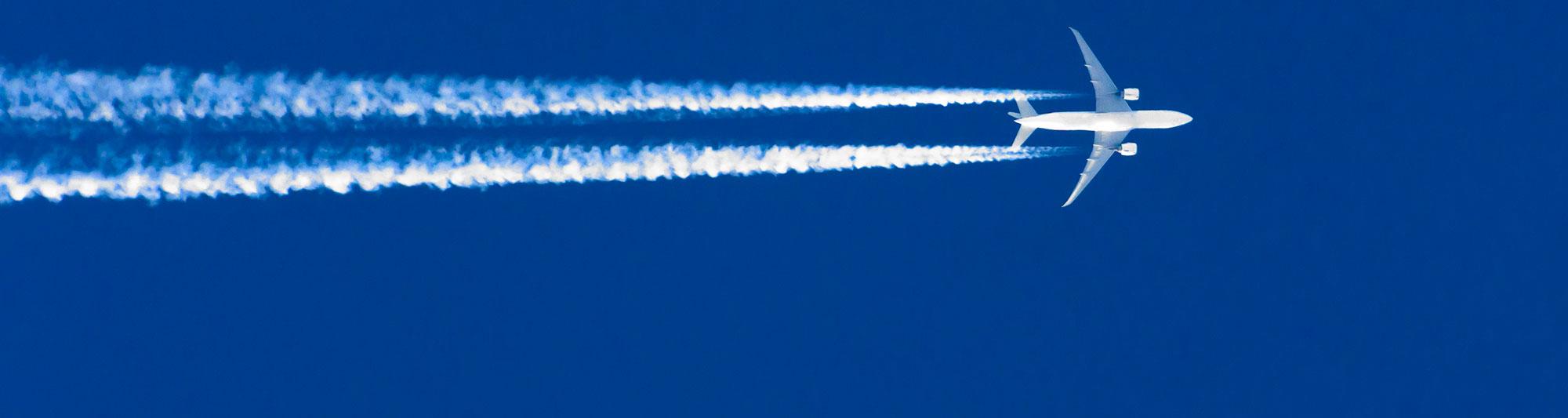 Flygplan med kondensstrimmor mot blå himmel